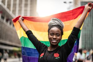 BIPOC person holding pride flag