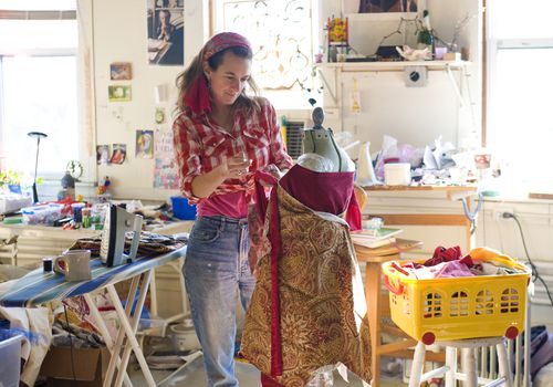 Woman making a dress in a messy room