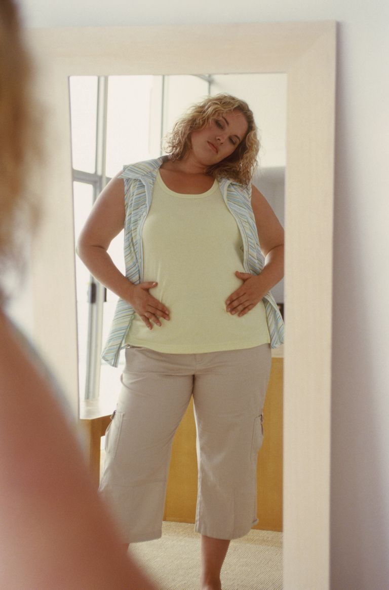 View of woman posing in mirror with hands on her stomach