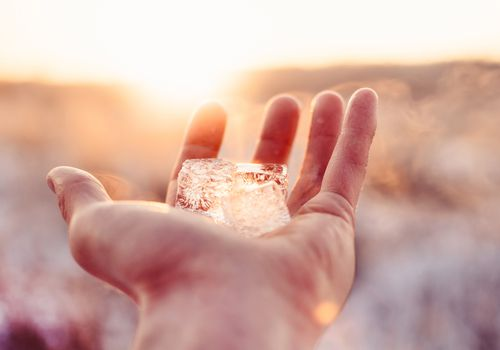 outstretched hand holding ice cube