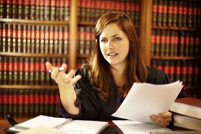 Woman in legal library holding papers and talking