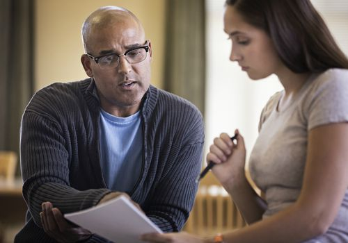 Male life coach talking to young woman and pointing to paperwork
