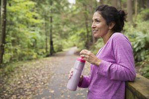 Smiling woman taking a break drinking water woods