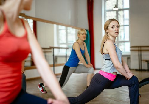 Three women doing a hip flexor stretch in a fitness class