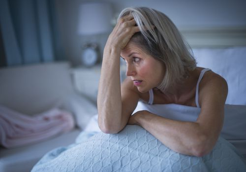 Distressed woman sitting up in bed in a darkened room