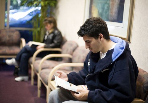 Teen male reading a magazine in a doctor's office waiting room