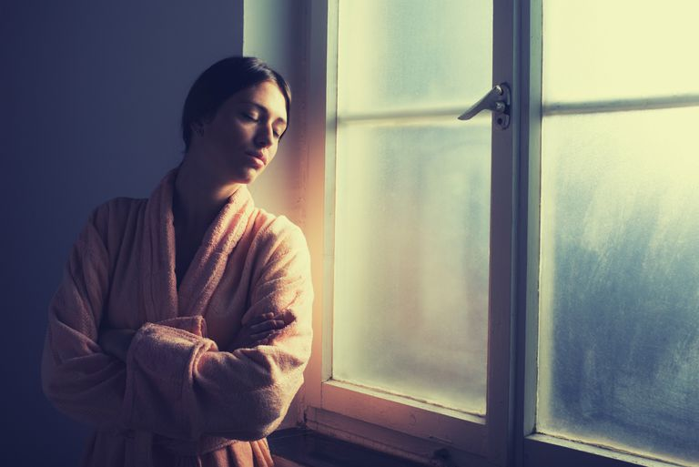 Anxious woman wearing a robe standing alone by the window