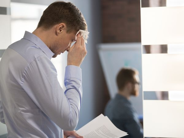 Nervous sweaty speaker preparing speech wiping wet forehead with handkerchief
