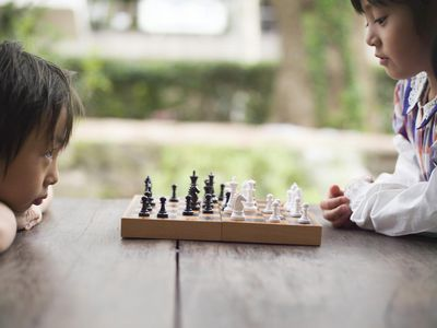 two asian children playing chess at a table outside