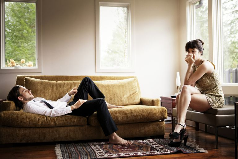 Unhappy couple not speaking to each other in living room