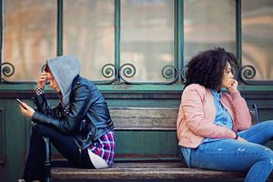 Girlfriends in conflict are sitting on the bench and sulking each other