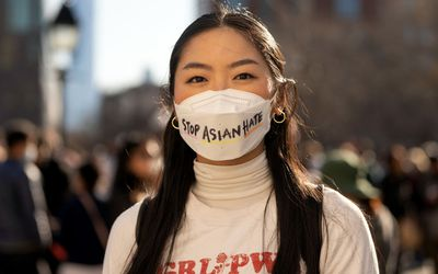 A woman standing outside wearing a mask that reads stop asian hate