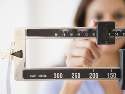 Person weighing themself on scale.