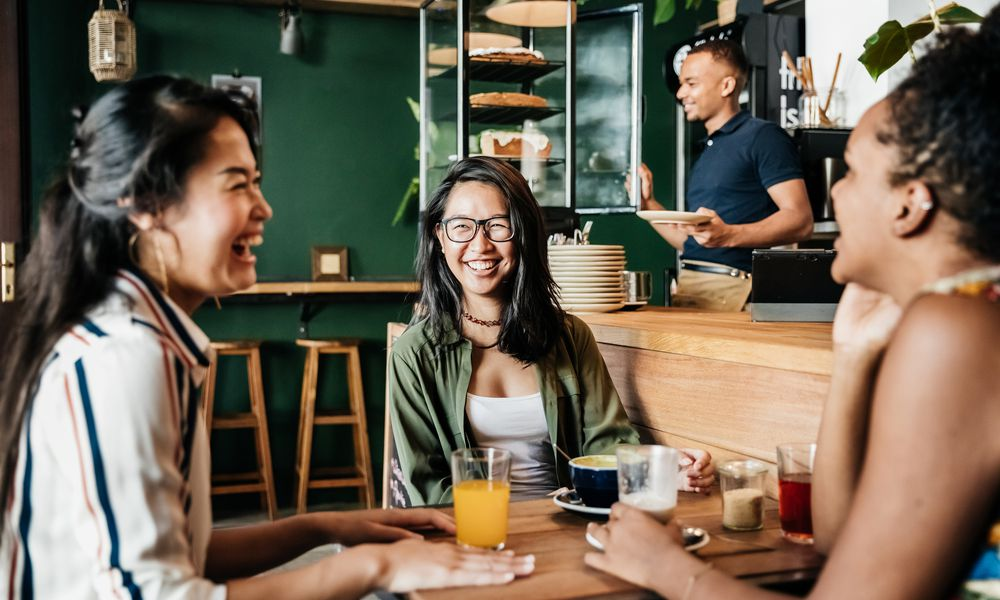 Three young friends sitting down in their favorite coffee shop, laughing and catching up with each other.
