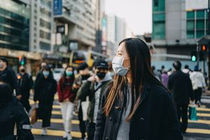 Asian woman long hair wearing a mask in the city.