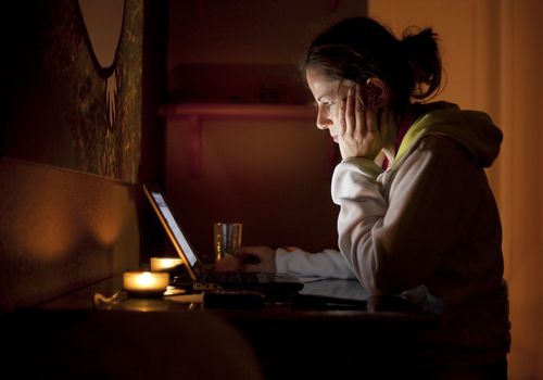 Woman looking at a computer in a darkened room