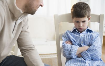Father looking at upset young boy