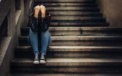 Depressed teen sitting on stairs