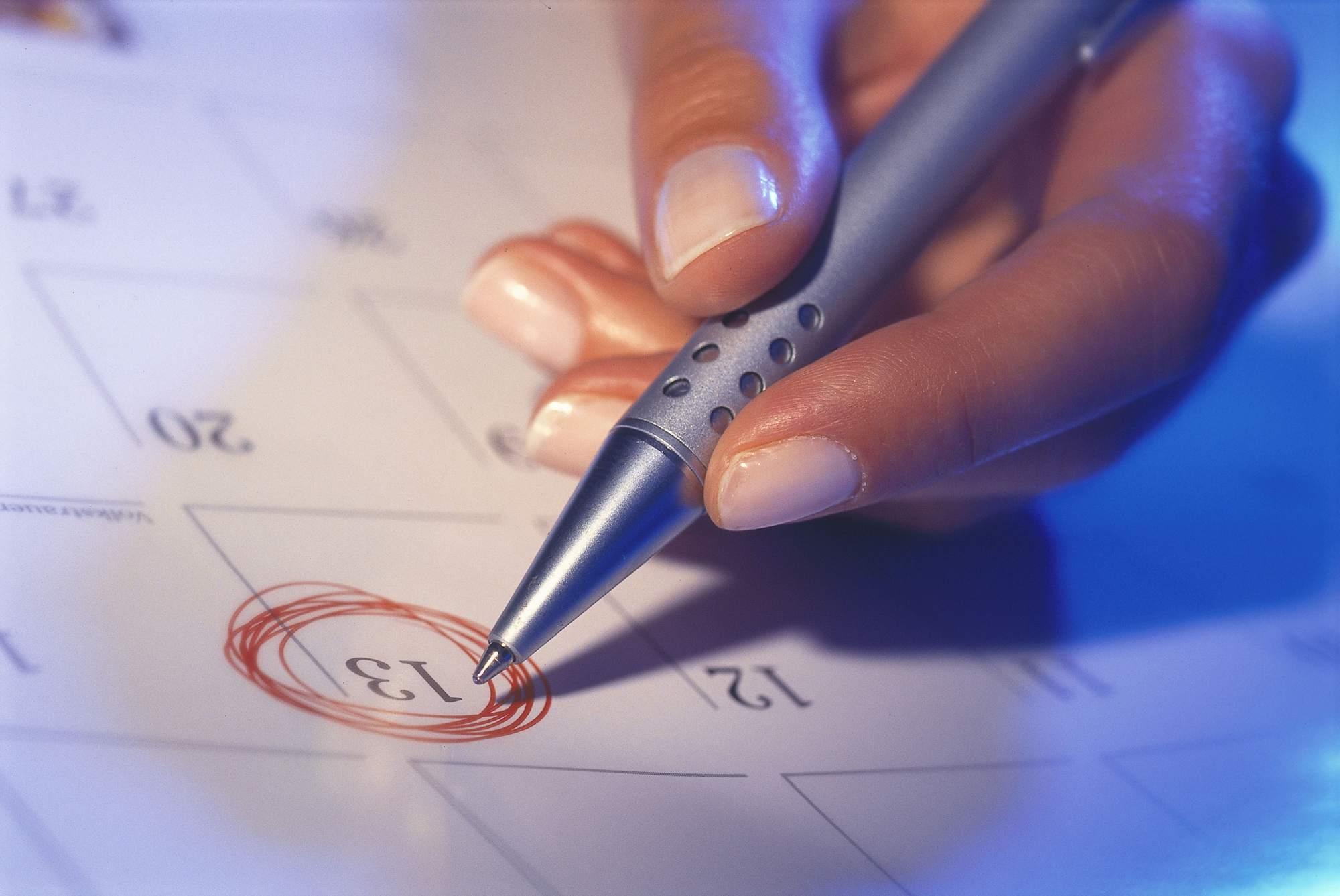 hand circling calendar date with pen