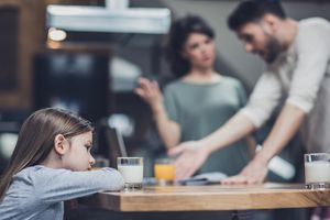 parents fighting while little girl sits at the table