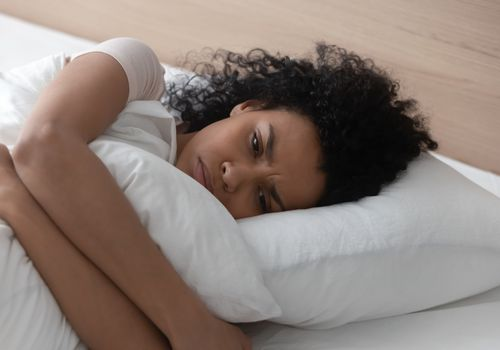 Sad depressed african woman hugging pillow lying in bed alone