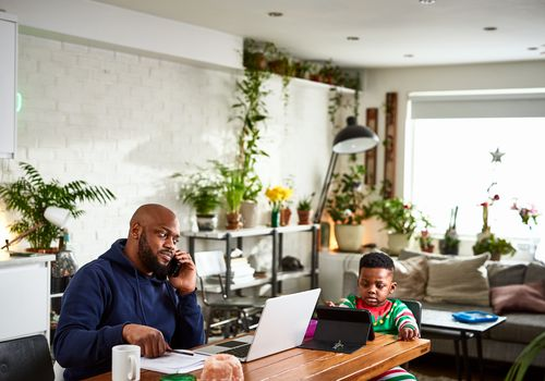 Man using phone, working from home at dining table while child uses tablet next to him