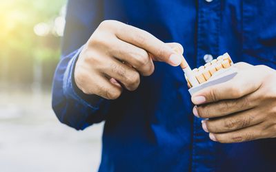 Close up of male hand taking a cigarette from pack