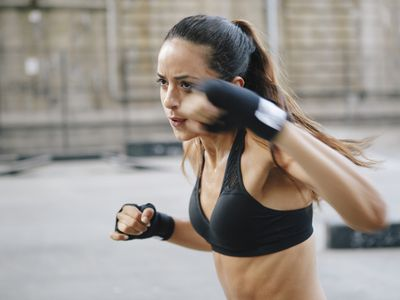 woman in sports bra throwing a punch