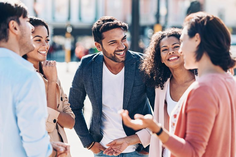 Group of smiling young people talking outdoors in the city