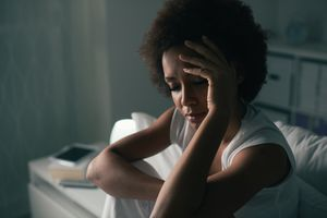 Sad depressed woman suffering from insomnia, she is sitting in bed and touching her forehead, sleep disorder and stress concept