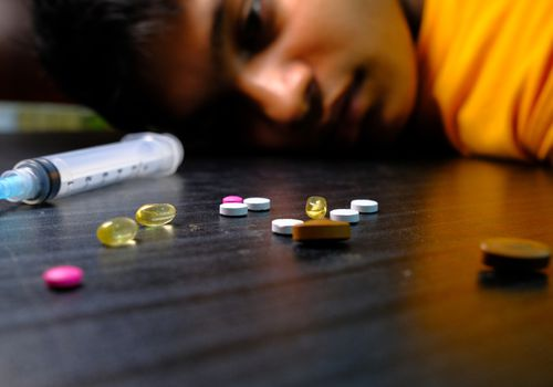 Youg man on floor next to assorted pills