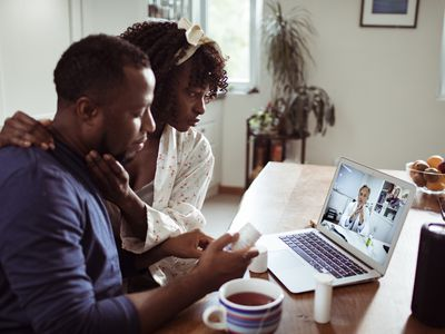 Close up of a young African couple consulting with their doctor over a video call on the laptop
