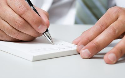 Doctor writing on a prescription pad