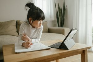 A young girl with black hair working on a computer with wireless headphones in.