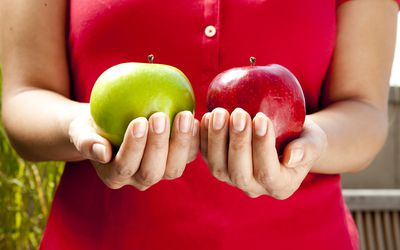 Woman comparing weights of apples