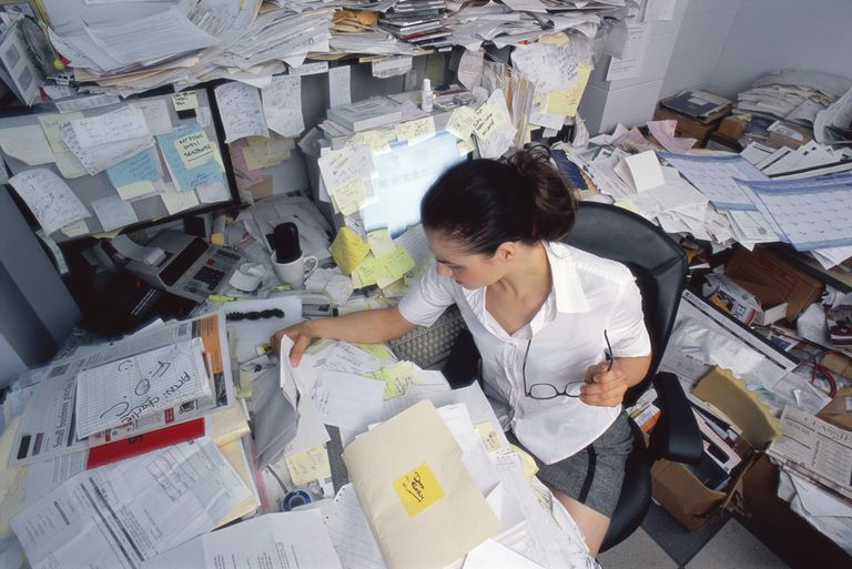 Businesswoman looking through papers on cluttered desk, elevated view