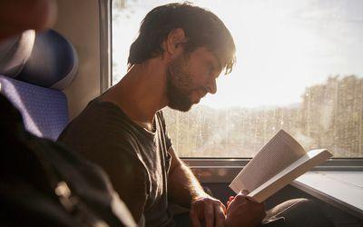 man reading book on train
