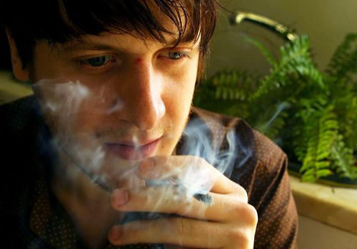 A man smokes marijuana at his home August 8, 2001 in the Dalston section of East London.