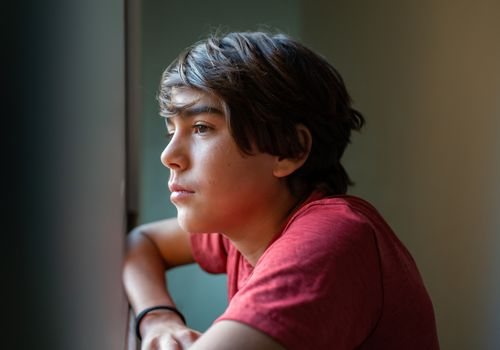 latinx preadolescent boy looking out through window, reflecting, relaxing, pensive
