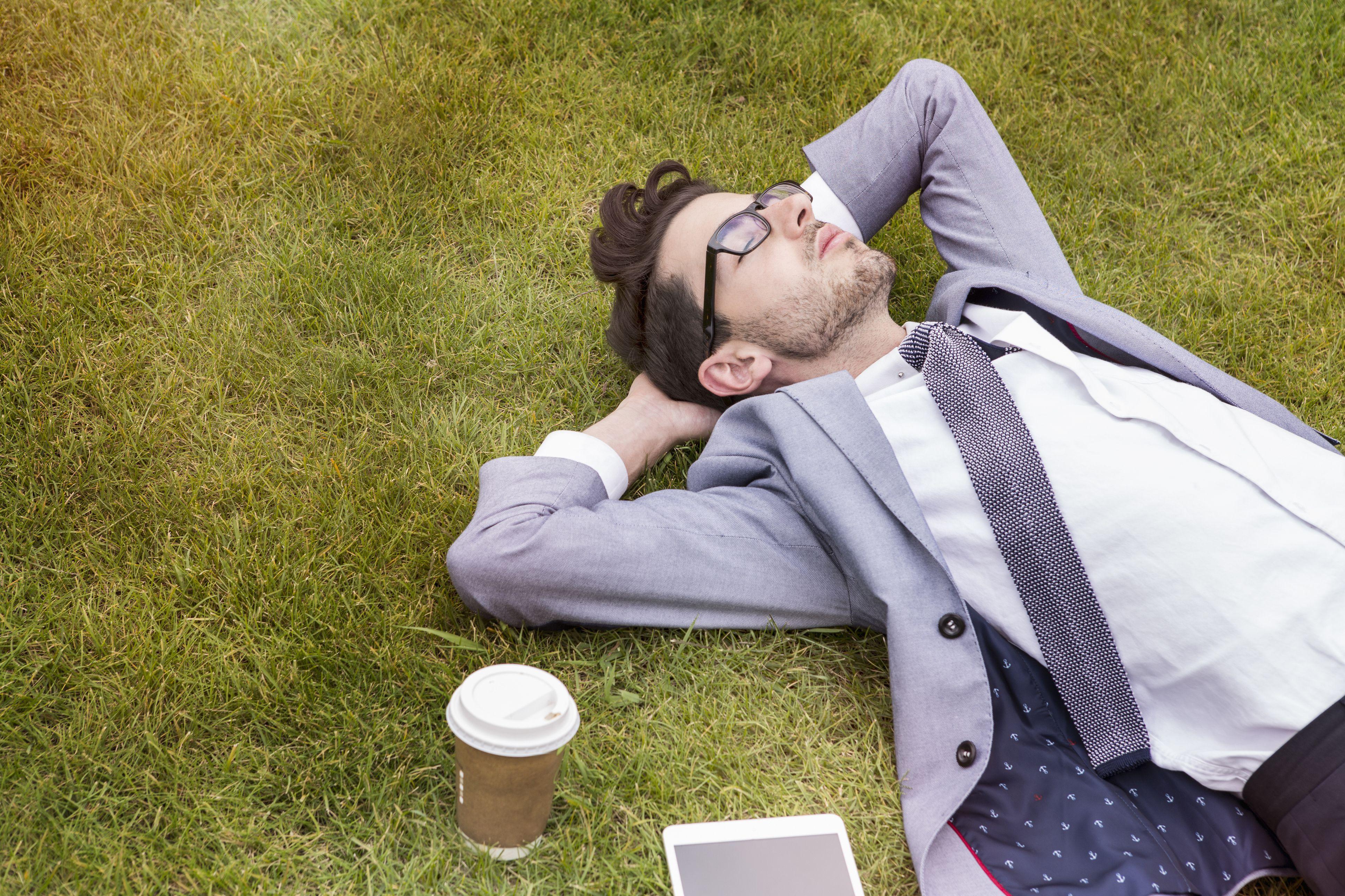 businessman having break, laying in grass
