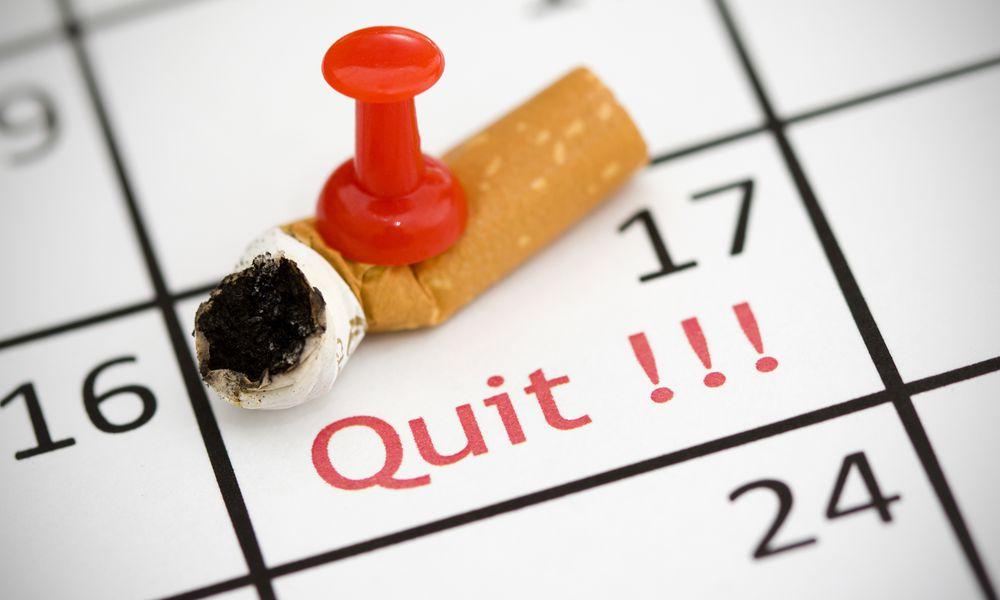 Cigarette butt pinned onto a calendar date marked quit