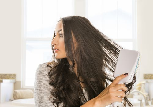 Woman brushing long dark, wavy hair with a large, flat hairbrush