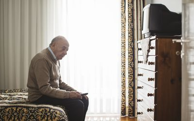 old man sitting on the bed looking sad