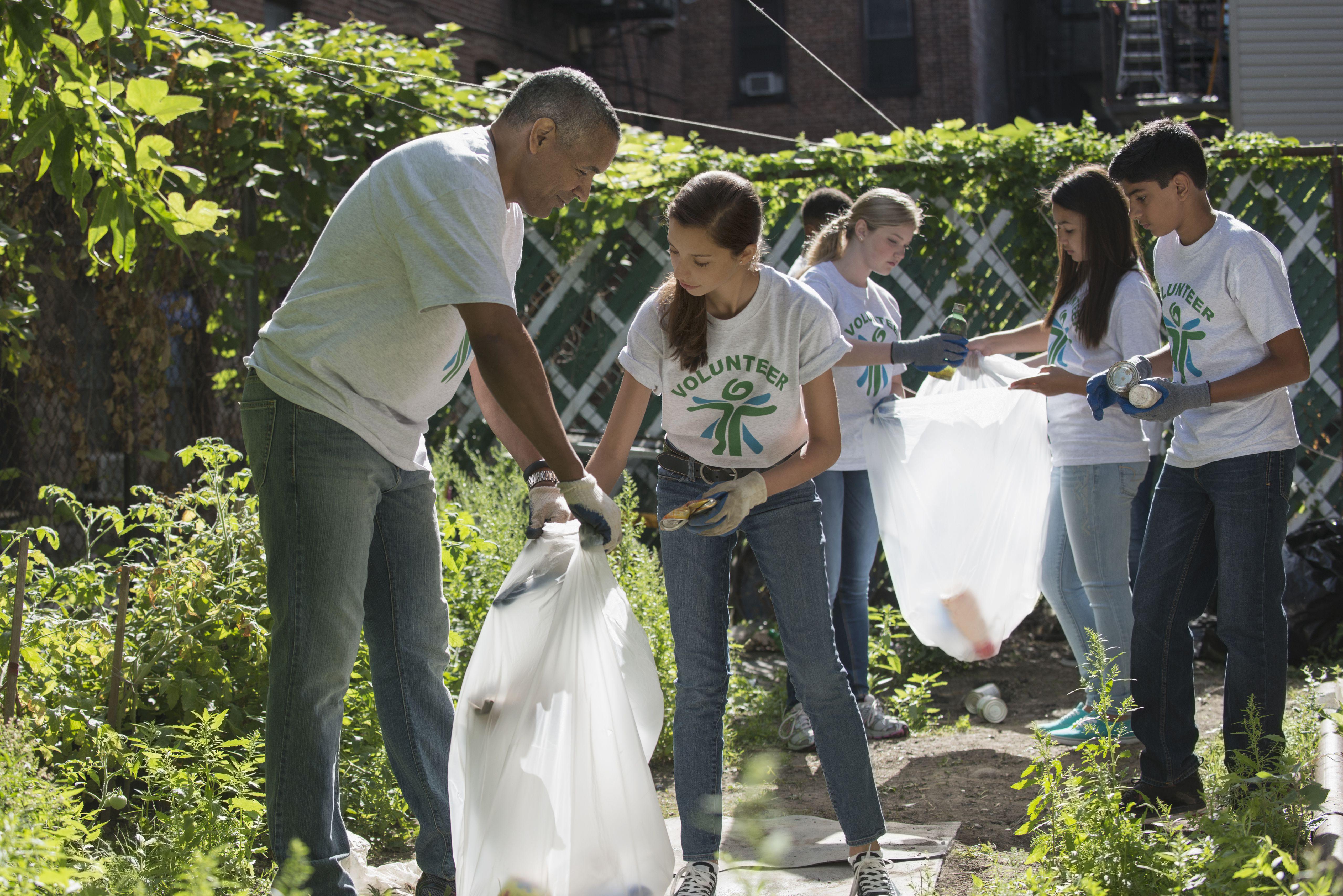 Volunteers picking up litter in urban garden