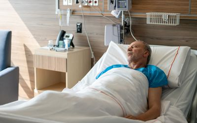 Man in hospital bed being treated for complications of end-stage alcoholism