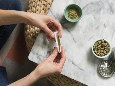 Hands of woman rolling marijuana joint