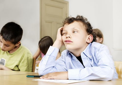 A boy sitting in class, head in hands.