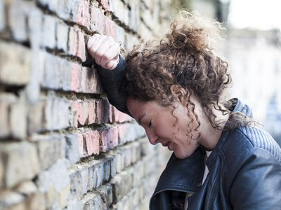 Profile of woman with curly brown hair leaning head against brick wall