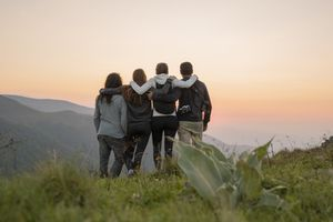 group of hikers standing on viewpoint at sunset