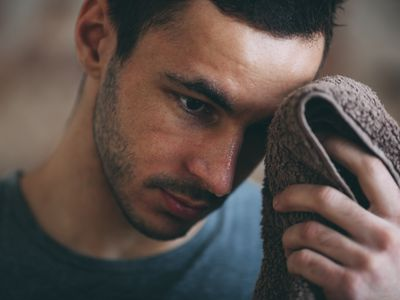 Sporty man wiping sweat on forehead at gym